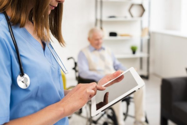 nurse-checking-her-tablet-close-up_23-2148239027